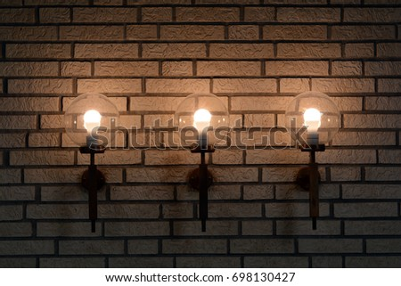 Round glass lamps in brick wall