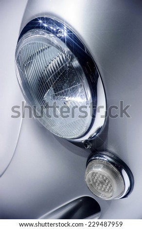 Round glass retro car headlights with chrome inserts on silver hood - stock photo