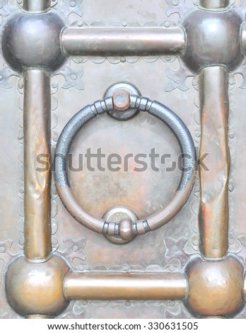 Round handle-the hammer on the bronze doors of the Church - stock photo