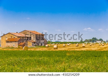 round hay bales in a harvested field near a country farmhouse, rural and bucolic atmosphere of a hot summer day
