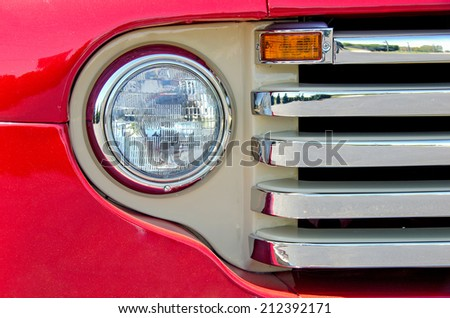 round headlight and chrome grill on a red antique pick up truck - stock photo