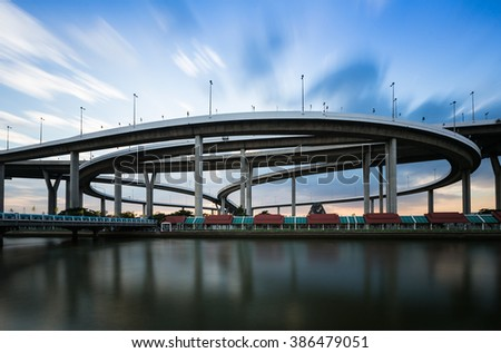 Round highway intersection road with moving cloud waterfront - stock photo