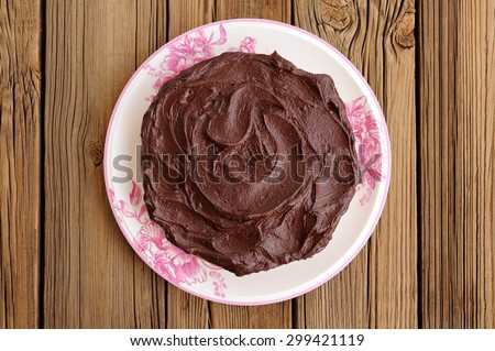 Round homemade chocolate cake covered with thick ganache in white plate on wooden table top view - stock photo