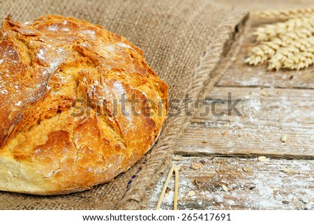 round loaf of traditional bread on wooden surface - stock photo