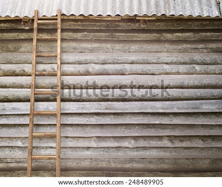 round log wall with a wooden ladder background - stock photo