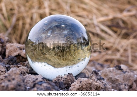 round magical crystal ball at field soil