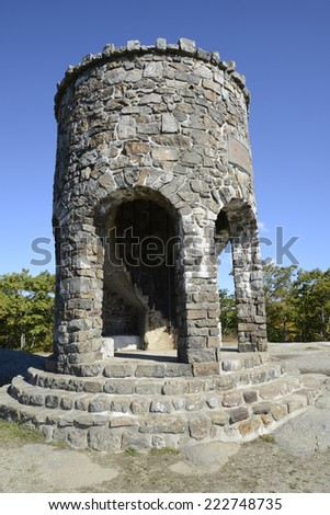 round observation tower at Mount Battie in Camden, Maine.  The structure is round and made of stones with an inside spiral staircase. There is a beautiful blue sky above the tower. - stock photo