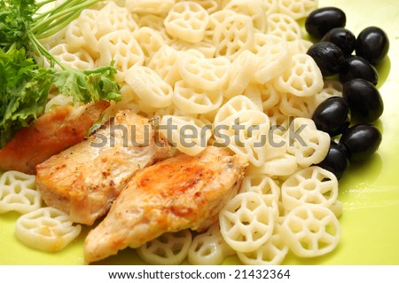 Round pasta with fried chicken, parsley and olives - stock photo