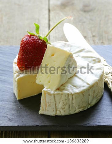 round piece of soft cheese with a white mold (brie, camembert) - stock photo