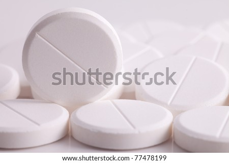 round pills paracetamol or aspirin painkiller remedy works against headache fever flu and pain a white pill medicine and the cure for illness a drug medicine - stock photo