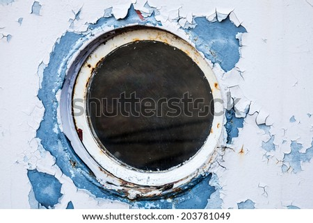 Round porthole in white and blue ship wall - stock photo