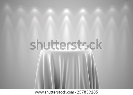 Round presentation pedestal covered with a white silk cloth in front of a wall illuminated by spot lights - stock photo