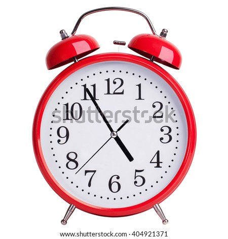 Round red alarm clock showing almost five - stock photo