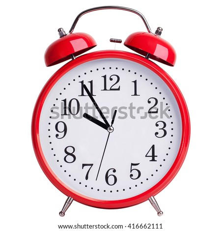 Round red alarm clock shows five minutes to ten - stock photo
