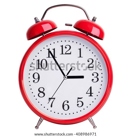 Round red alarm clock shows five minutes to three - stock photo