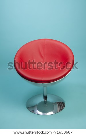 Round Red Retro Chair with chrome Pedestal on blue background - stock photo