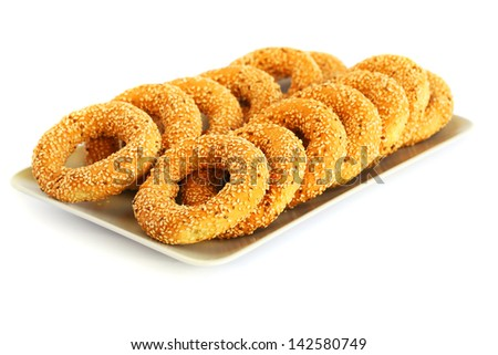 Round rusks with sesame seeds on tray.