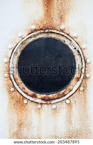 Round rusted porthole on white ship wall - stock photo