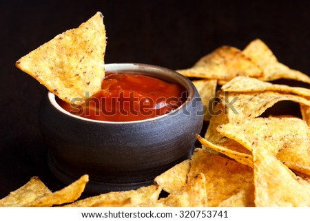 Round rustic brown bowl of tomato salsa dip surrounded with tortilla chips in perspective. Black background.
