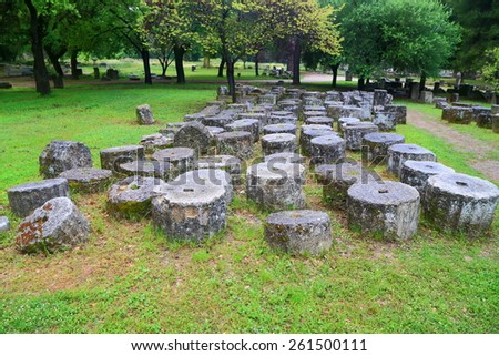 Round segments of ancient columns laying on the ground, Olympia, Greece - stock photo