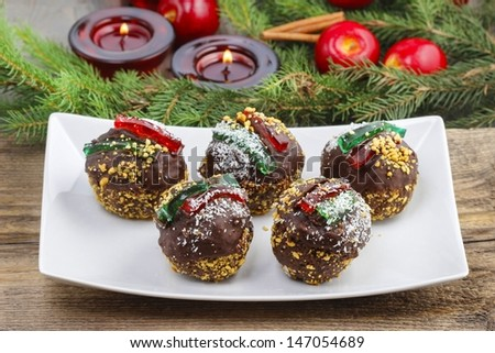 Round shape chocolate christmas cakes, decorated with jelly strips, nuts and coconut. Christmas tree, apples and lanterns in the background. - stock photo