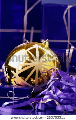 round shiny Christmas ornament on the violet ribbon and gift boxes for background ... - stock photo
