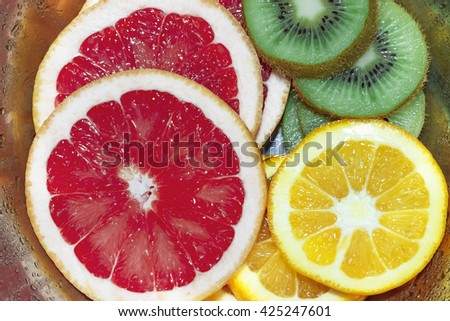 Round slices of grapefruit, orange and kiwi in the iron bowl  with drops. Fresh, ripe, juicy fruit.  - stock photo