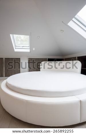Round spacious bed in designed house, vertical