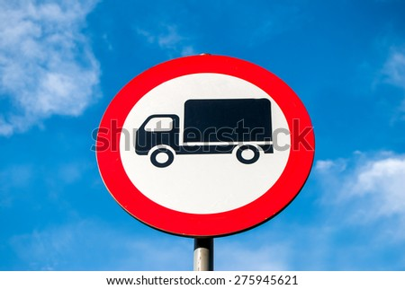 Round speed limit trucks road sign above blue cloudy sky