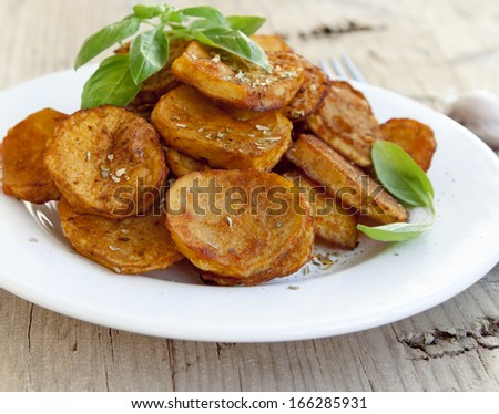 Round spicy baked potatoes with condiments and basil leaves - stock photo