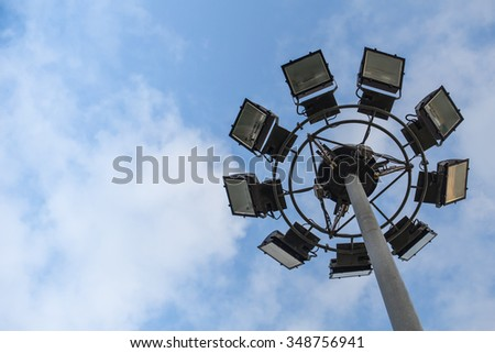 Round sport light with blue cloud sky background with space for text. - stock photo