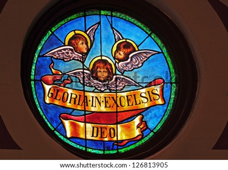 Round stained glass window of angel faces with Christmas message in Latin of Gloria in Excelsis Deo - stock photo