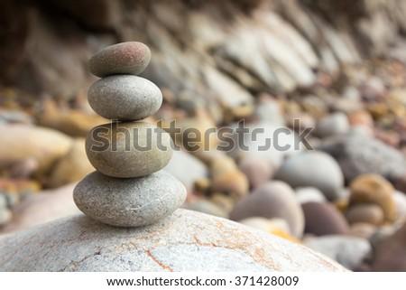 Round stones decorative colors stacked on beach - stock photo