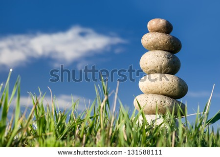 Round stones lays on a grass. Blue sky on a background