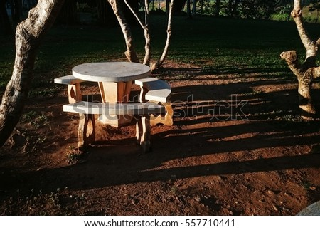 round table stone bench with morning sunlight