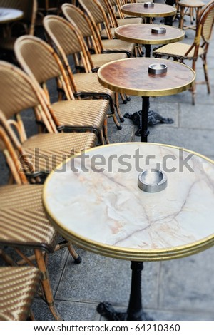 Round tables and chairs in cafe in Paris. Photo with tilt-shift effect - stock photo