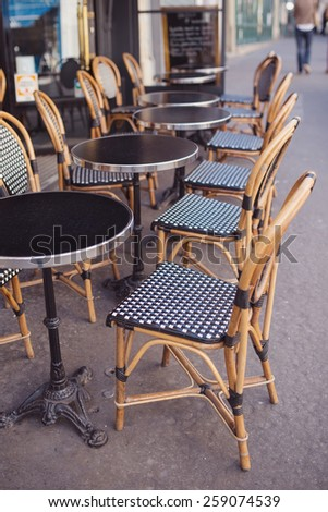 Round tables and wicker chairs in a cafe in Paris, France. - stock photo