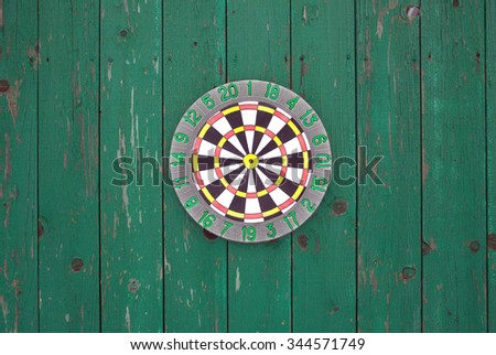 Round target for darts hanging on old wooden fence painted green color