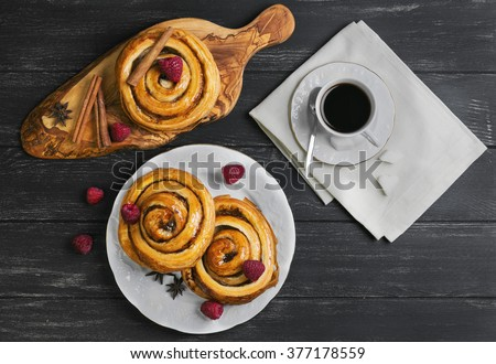 Round twisted Denish Buns with berries raspberries, syrup, white cup espresso coffee, sugar cubes, cinnamon sticks, star anise, cutting board made of wood olive on a black wooden background, top view - stock photo