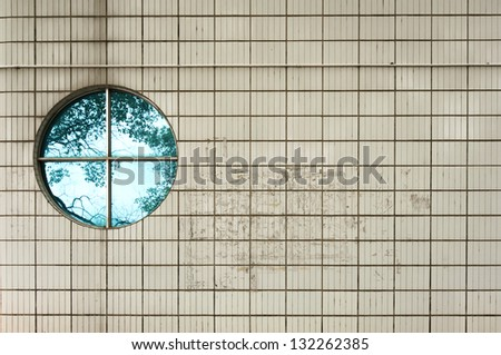 Round  vintage  window on ceramic tile wall building with tree reflection - stock photo
