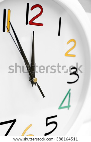 Round wall clock with colorful figures, close up