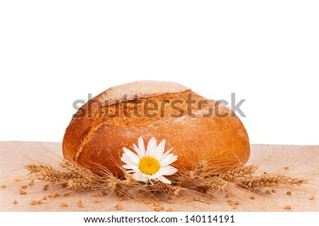 Round white bread on a burlap over white background - stock photo