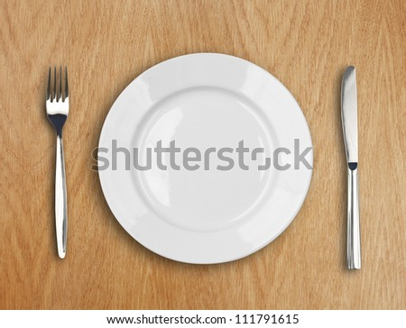 round white plate, knife and fork on wooden table - stock photo