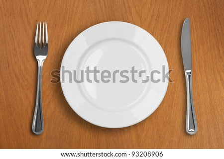 round white plate, knife and fork on wooden table