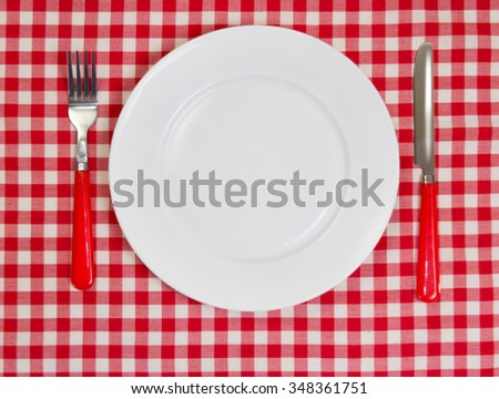 Round white plate on red cloth. Clean dish with dishware.Fastfood concept.