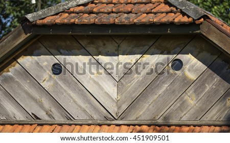 round windows on the wooden pediment tile roof  - stock photo
