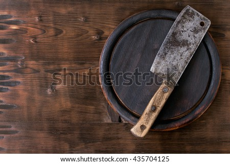 Round wood Chopping cutting board with vintage butcher cleaver over dark wooden background. Top view with copy space - stock photo