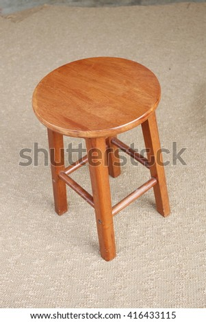 Round wooden chair without a backrest, on brown background. (Light from right to left. Shadows appear on the left side of the object.)