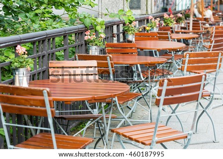 round wooden tables with chairs at summer open air cafe terrace