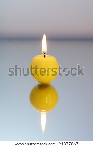 Round yellow candle burning on a reflective surface. - stock photo